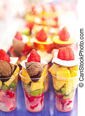 Fruits pieces in a plastic cup take away ready to eat on a...