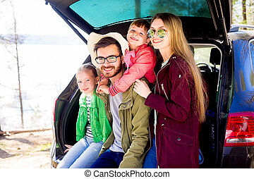 Family going on a car trip - Happy family of four going on a...