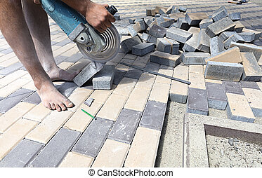 Worker cuts paving slabs for laying on the terrace