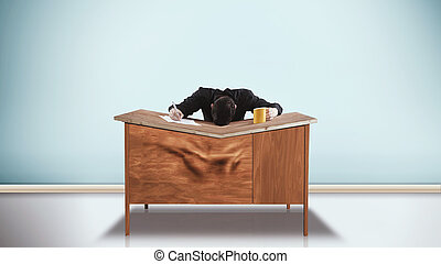 Bent desk - A man has dropped his head onto his desk and the...