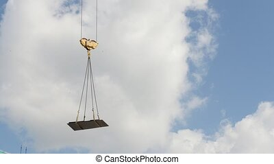 A crane lifting heavy equipments on a construction site - in...