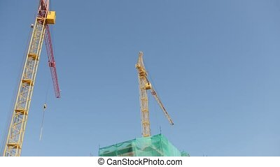 Working cranes on construction site, time-lapse