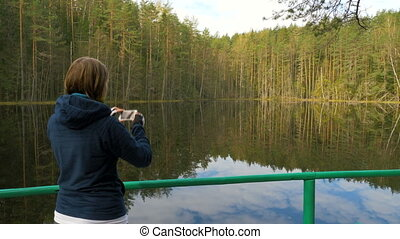Girl make a picture using phone in the forest.
