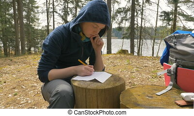 Girl are writing notes on the stump in the forest