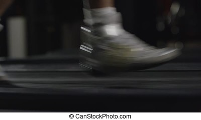 Man running in a modern gym on a treadmill concept for exercising, fitness and healthy lifestyle. Exercising on treadmill. Close-up of man walking by treadmill in sports club. Legs of sportsman running on treadmill: sport and healthy lifestyle concept
