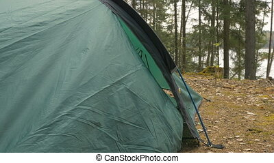 Girl looks out of the tent in the forest.