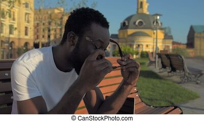 Radiant young man putting on glasses while sitting on bench...