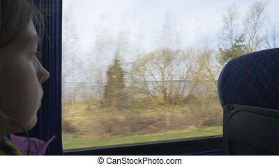Enjoying travel - young girl traveling by bus and sitting near the window