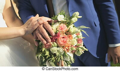 Hands of the bride and groom with wedding rings