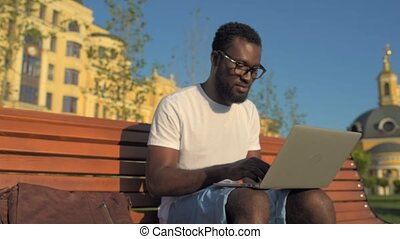 Positive African American man using computer for project...