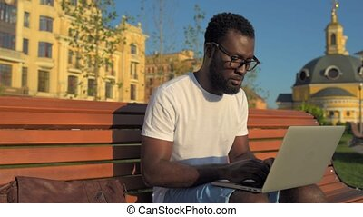 Serious millennial man working on laptop outside - High...