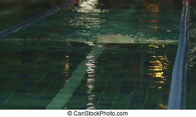Young man swimming the front crawl in a pool. Dynamic and fit swimmer breathing performing the butterfly stroke. Professional male swimmer in a pool
