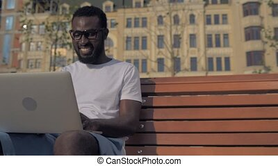 Cheerful man having rest after working long hours on laptop...