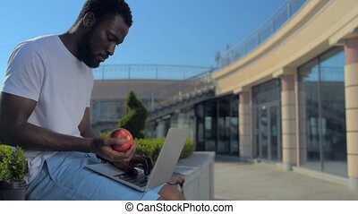 Handsome young man with laptop throwing apple up - Vitamins...