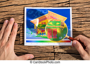 Person Analyzing The Heat Loss Of A House - Person Analyzing...