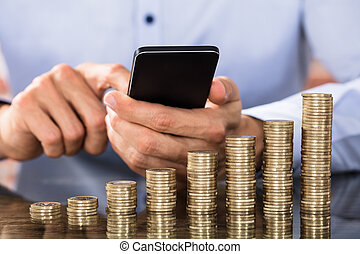 Businessman Using Smart Phone For Calculating Coins - Stack...