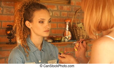 makeup artist paints the eyes young beautiful girl with hair...