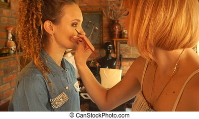 beautiful young curly girl sits on a Chair and make-up makes...