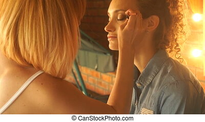 makeup artist makes eye makeup young girl
