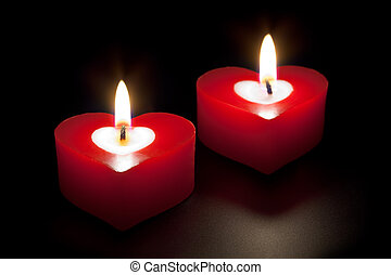 Heart shaped candles isolated on black background