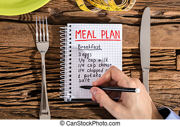 Elevated View Of Human Hand Making Meal Plan On Notebook -...