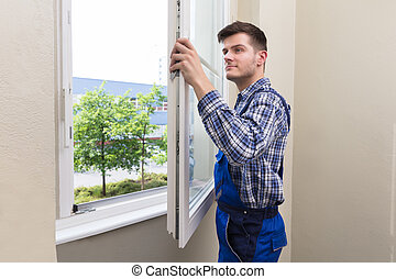 Handyman Installing Window - Young Male Handyman In Uniform...