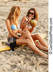 Two beautiful sporty surfer girl at the beach. - Portrait of...