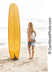 Beautiful sporty surfer girl at the beach. - Beautiful...