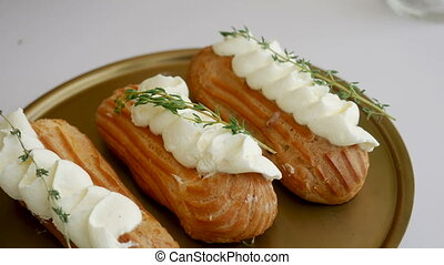 eclairs are on a gold plate on the festive table