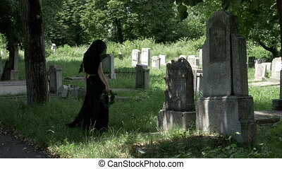 Woman filled with sadness looking from lost beloved grave...