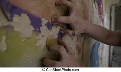 Closeup of woman hands and fingers scratching a ruined wall
