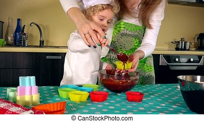 Mother and cute little daughter are smiling while filling...