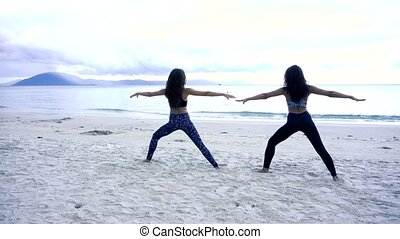 Women with a slender figure are engaged in gymnastics at sea