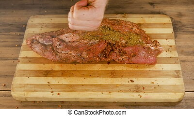 A man cooks meat on a cutting Board on the table from old...