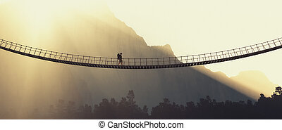 Man with backpack on a rope bridge