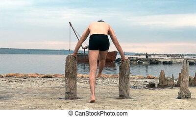 Man Athlete Doing Warm-up On Wooden Pillars.