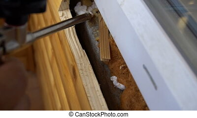 Nozzle of construction gun fills space under window frame by polyurethane foam or with mounting foam