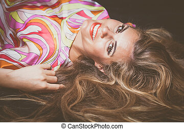 young smiling woman with long blonde hair lie down studio...