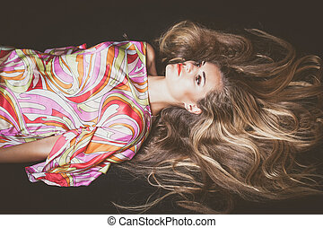 young woman with very long blonde hair lie down studio shot...