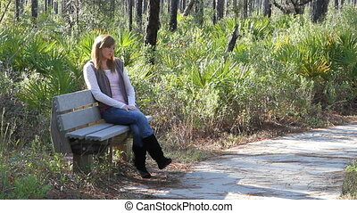 Teen Depression - Teenager sits on a park bench in a state...
