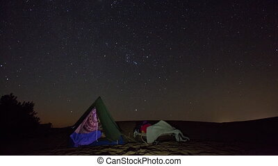 Timelapse of a person sleeping under a starry sky. The night...
