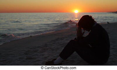 Praying At Sunset - Mature woman sits on the beach praying...