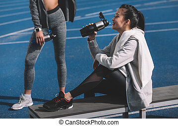 Athletic young women in sportswear drinking water from sports bottles on stadium, running women concept