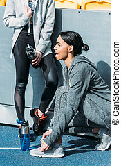 Athletic young women in sportswear resting with sports bottles on stadium, running women concept