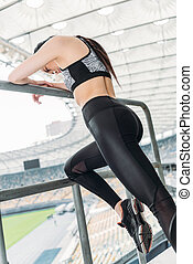 young asian sportswoman in sportswear stretching at handrail on stadium