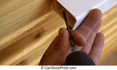 a worker fixes installed window sill using the screws
