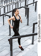 Young fitness woman in sportswear running up on stadium stairs