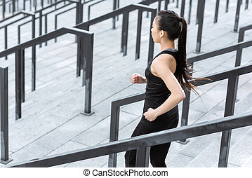 Young fitness woman in sportswear running down on stadium stairs
