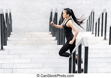 Side view of attractive young asian woman in sportswear jogging on stadium stairs