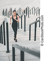 Young asian woman in sportswear running up on stadium stairs